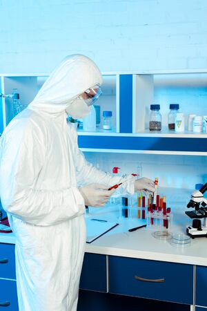scientist in latex gloves holding syringe and test tube with coronavirus lettering Archivio Fotografico