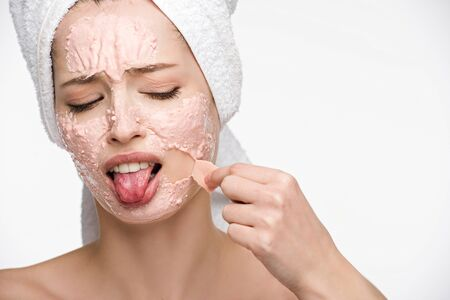 displeased girl removing peeling mask from face and sticking out tongue isolated on white