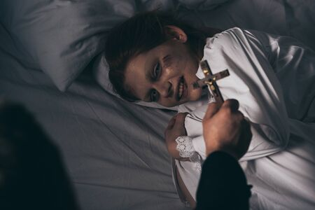 exorcist holding cross over demonic obsessed smiling girl in bed Stock Photo