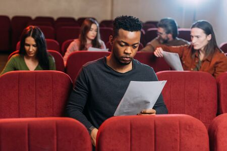 african american actor reading screenplay on seats in theatre