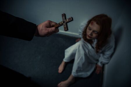 exorcist holding cross in front of obsessed girl Stock Photo