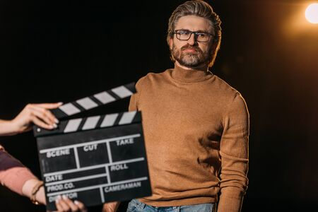 selective focus of mature actor with clapboard in front