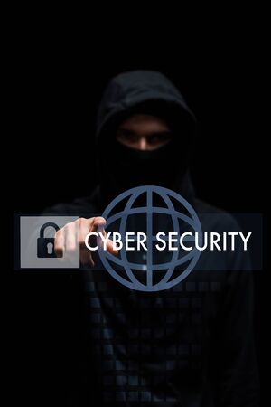 selective focus of hacker in hood pointing with finger at cyber security lettering on black