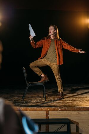 handsome actor with screenplay playing on stage during rehearse in theatre
