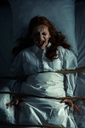 female yelling demon in nightgown bound with rope in bed