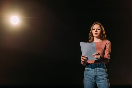 beautiful young actress reading scenario on black
