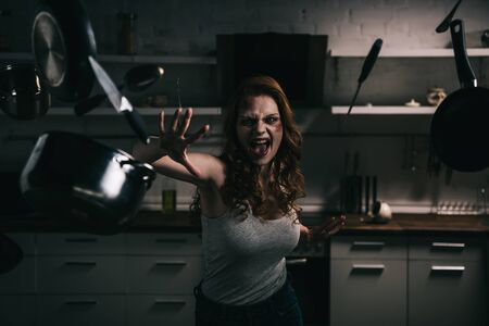 demoniacal shouting girl gesturing with levitating kitchenware in kitchen Stock Photo