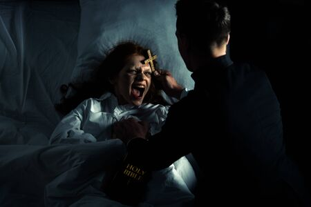 exorcist with bible and cross standing over demoniacal yelling girl in bed