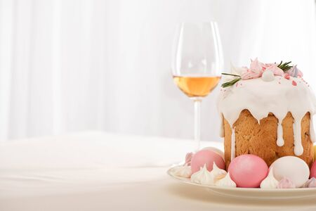 delicious Easter cake decorated with meringue with pink and white eggs on plate near wine glass