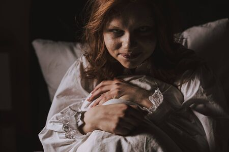 demoniacal smiling woman in nightgown sitting in bed Stock Photo
