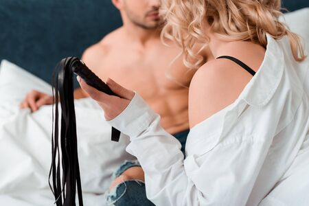 selective focus of woman holding flogging whip near muscular man