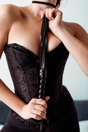 cropped view of dominant young woman in corset holding flogging whip