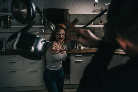 selective focus of creepy demon with levitating cookware and exorcist with cross in kitchen Stock Photo