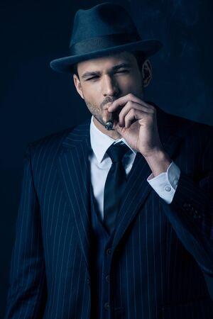 Front view of mafioso smoking cigar on dark background 免版税图像