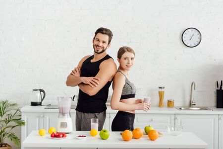 sportive man with crossed arms near happy woman with smoothie in glass Stock Photo