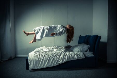 demonic girl in nightgown levitating over bed
