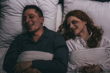 top view of smiling female demon lying in bed with man