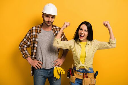 successful excited female manual worker with hands up near coworker on yellow