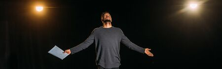 panoramic shot of african american actor holding scenario and standing on stage during rehearse Imagens