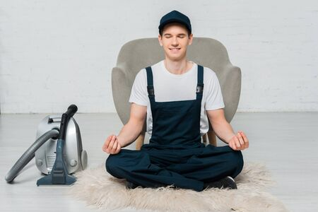 happy cleaner in cap meditating on carpet near vacuum cleaner and armchair