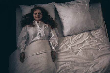 top view of creepy smiling demon in nightgown lying in bed
