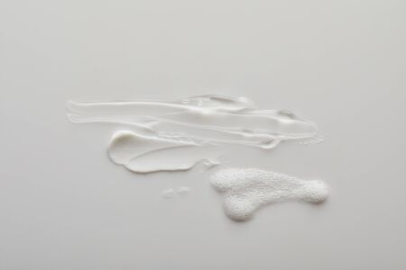 Top view of gel and cosmetic cream brushstrokes with soap foam on grey background