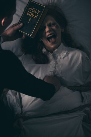 exorcist with bible and obsessed screaming woman in bedroom