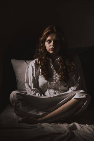 demonic young woman in nightgown sitting in bed Stock Photo