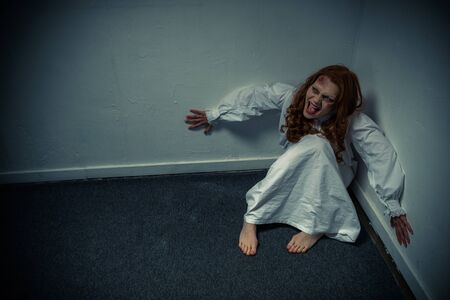 obsessed demonic girl in nightgown yelling and sitting near wall Archivio Fotografico