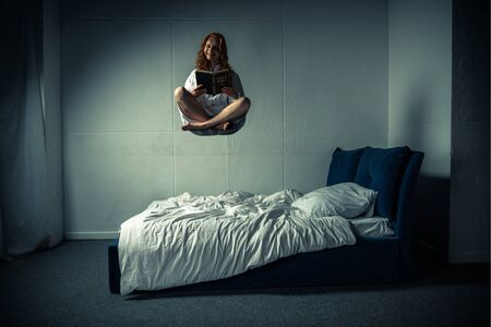 creepy smiling girl in nightgown levitating over bed while reading bible