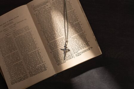 top view of open holy bible with cross on dark background with sunlight