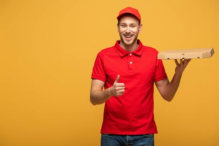 happy delivery man in red uniform holding pizza box and showing thumb up isolated on yellow
