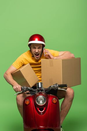 angry delivery man in yellow uniform on scooter with boxes talking on smartphone isolated on green