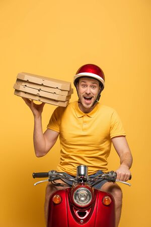 excited delivery man in yellow uniform riding scooter with pizza boxes isolated on yellow 免版税图像
