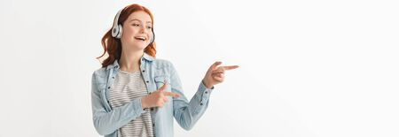 panoramic shot of excited female teenager listening music with headphones and pointing isolated on white