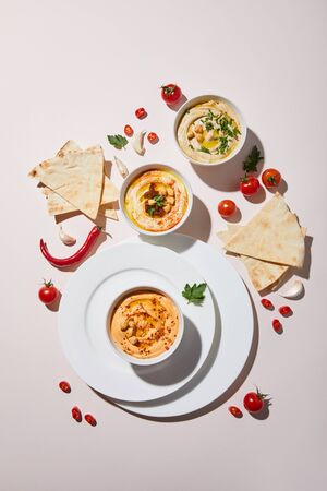 Top view of plates and bowls with hummus, fresh vegetables and pita bread on grey background
