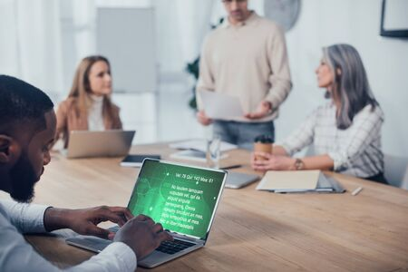 selective focus of african american man using laptop with health website and his colleagues talking on background Imagens