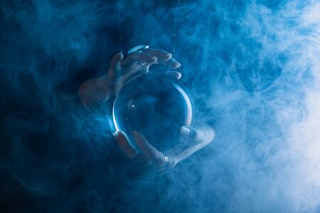 Partial view of witch holding crystal ball with smoke around on dark blue