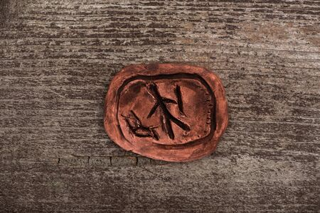 Top view of clay talisman with symbol on wooden background