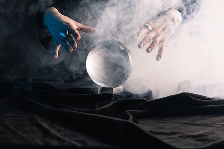 Cropped view of witch performing ritual with crystal ball on dark background 免版税图像