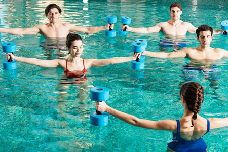 Trainer holding barbells while exercising with group of young people in swimming pool Reklamní fotografie