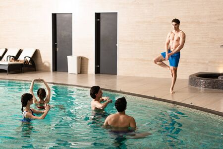 Handsome trainer standing on one leg while showing exercise to young people in swimming pool
