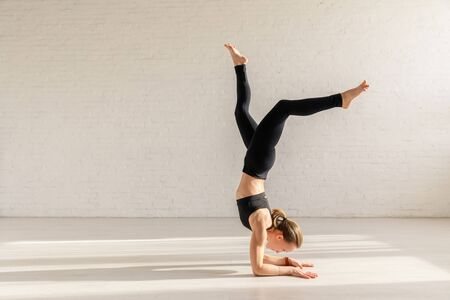 young woman doing supported headstand exercise in yoga studio Foto de archivo