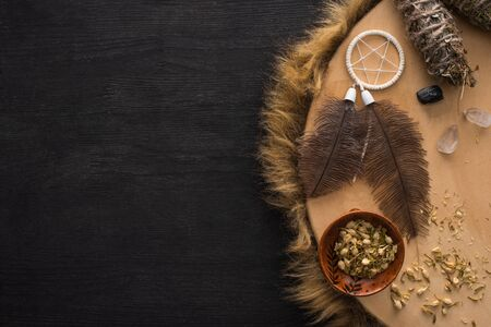 Top view of smudge sticks near dreamcatcher with feathers and crystals on shamanic tambourine on dark wooden surface