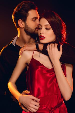 Handsome man embracing and kissing elegant girlfriend in red dress isolated on black Foto de archivo