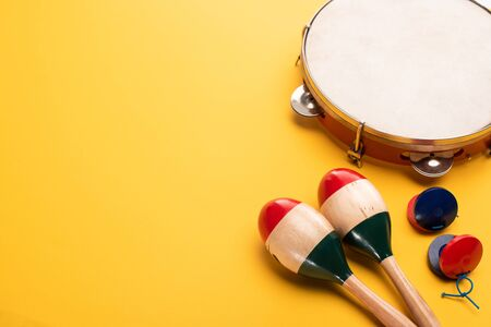 Wooden colorful maracas with tambourine and castanets on yellow background