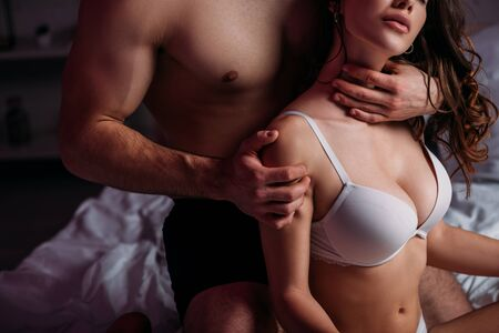 cropped view of shirtless man making neck and shoulders erotic massage to sexy girl with big breast in bra Banque d'images