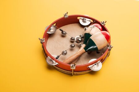 Wooden colorful maracas on tambourine on yellow background