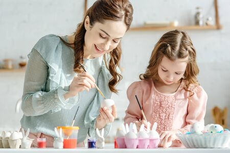 cheerful mother and happy child painting easter eggs near decorative bunnies