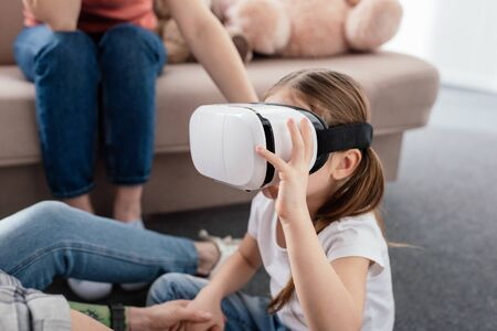 Kid using vr headset near mothers in living room 스톡 콘텐츠 - 142572192